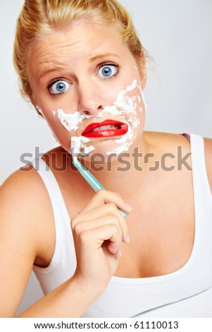 young funny woman with shaver on her face - stock photo