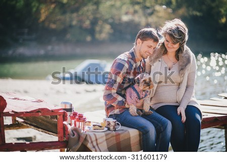 Young future parents and their dog in a funny costume sitting on a wooden bridge and having picnic near lake. Autumn time. Pregnancy