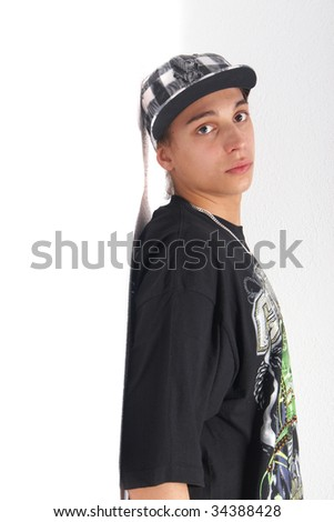 Young gangster leaning against a wall isolated over white.