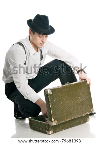young gangster sits and stares into an opened suitcase. isolated on white