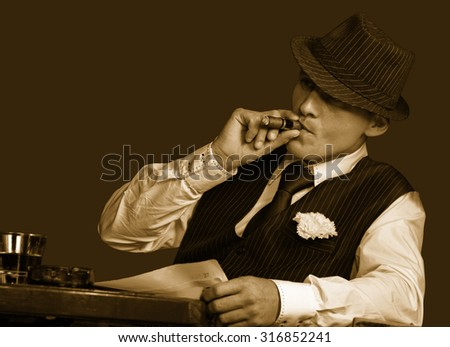 young gangster with hat smoking cigar, studio shot, sepia toning - stock photo