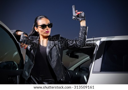 Young gangster woman with gun near the car - stock photo