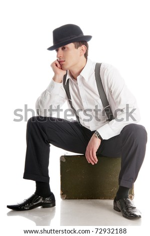 young gankster sitting on a suitcase and waits. isolated on white