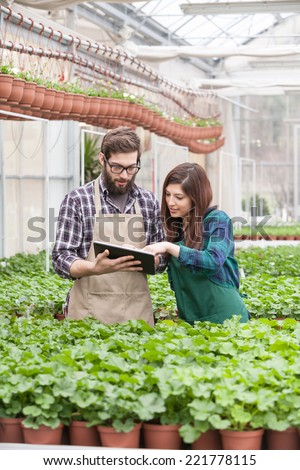 Young garden worker in apron using digital tablet at greenhouse - stock photo
