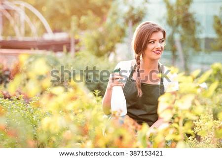Young gardener in green apron sprinkling plants, garden - stock photo