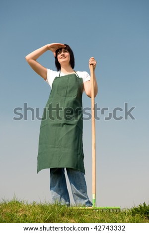 Young gardener standing in the meadow in front of blue sky - stock photo