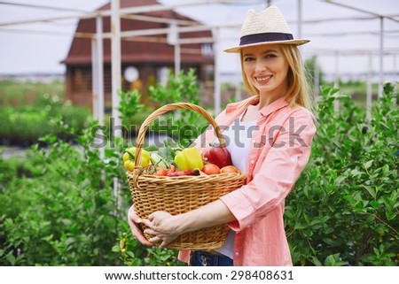 Young gardener with basket of various vegetables