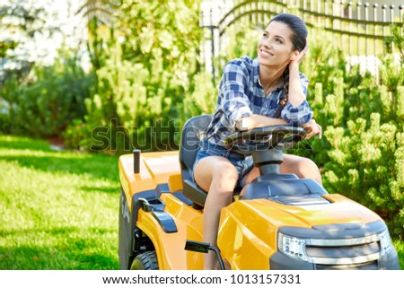 Young gardener woman mowing the grass