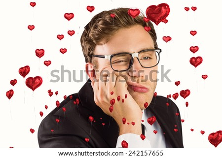 Young geeky businessman looking bored against red heart balloons floating - stock photo