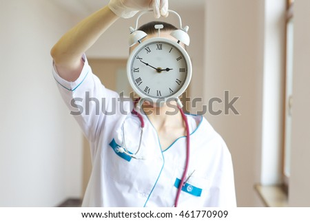 Young general practitioner stays in the corridor of a hospital with a alarm clock