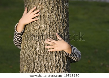young generation embracing nature, with a hug at a tree - stock photo