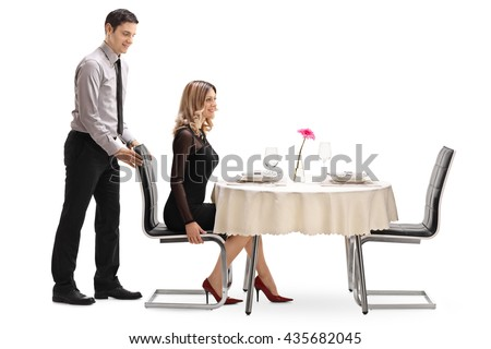 Young gentleman helping his girlfriend with the chair at a restaurant table isolated on white background - stock photo