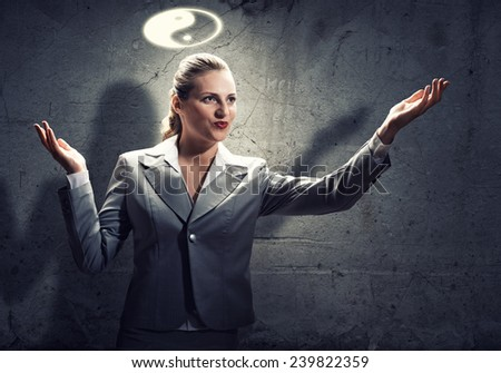 Young gesturing businesswoman with yin yang sign above head