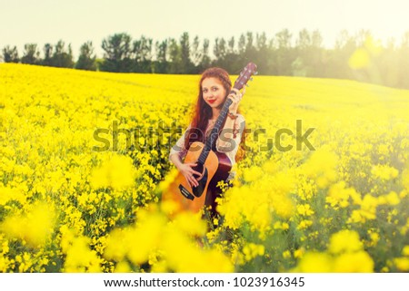 Young ginger hair girl in 70s style with acoustic guitar in rapeseed field.