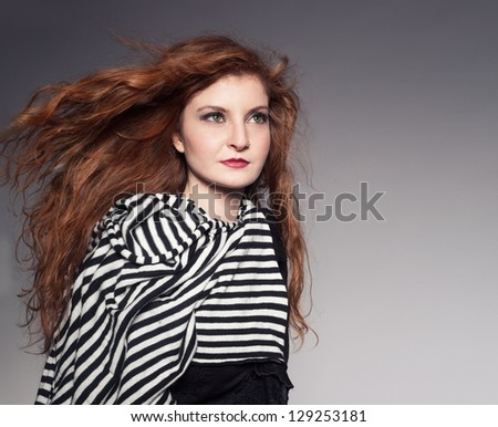 young ginger model wearing a black and white scarf posing in studio on grey background - stock photo