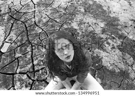 Young ginger woman alone in the darkness on dry craced desert   view from the top - stock photo