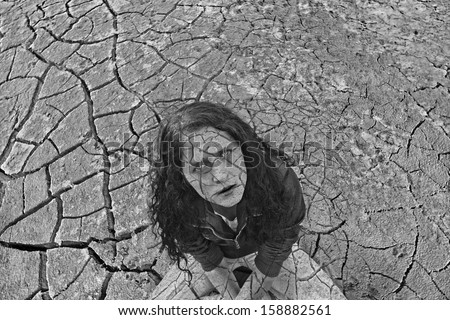 Young ginger woman alone in the darkness on dry craced desert view from the top White and black Copy space for inscription  - stock photo