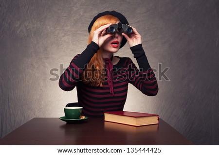 young ginger woman using binoculars found something interesting on grunge background - stock photo