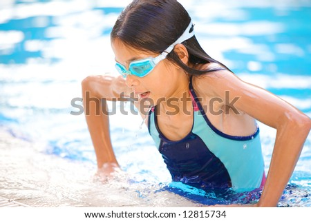 Young girl about to pull herself out of the swimming pool after a good swim - stock photo