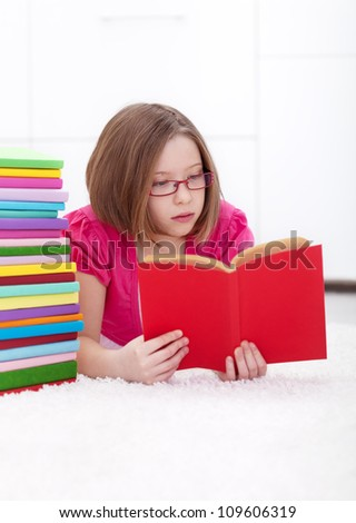 Young girl absorbed by a good book - reading and learning concept - stock photo
