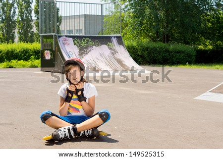 Young girl adjusts her protective head ware before continuing to practice rollerblading - stock photo