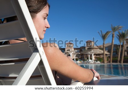 young girl against swimming pool at resort hotel