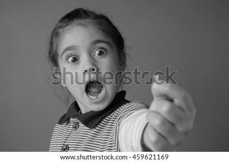 Young girl (age 6) surprise to find that she have lost her first bottom front milk teeth. Childhood healthcare concept. real people copy space (BW) - stock photo