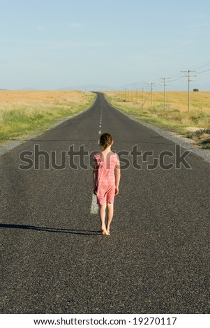 Young girl, aged seven, wearing a pink dress, walking down an endless road.