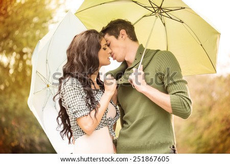 Young girl  and a boy standing embracing under umbrellas and they kiss. In the background is greenery. - stock photo