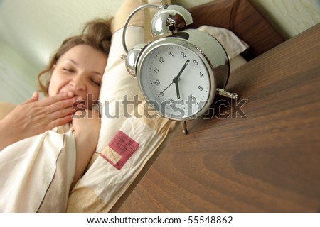 Young girl and alarm clock. Bedtime scene - stock photo