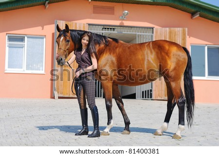 Young  girl  and  bay horse near stable - stock photo