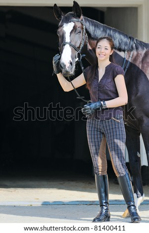 Young  girl  and black sport horse - stock photo