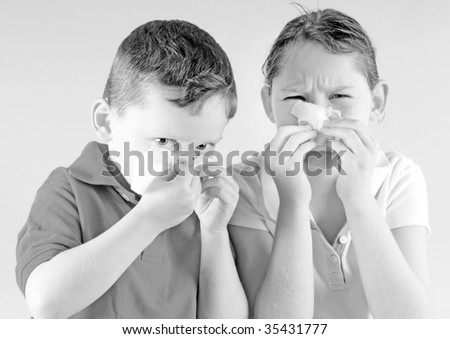 Young girl and boy blowing noses with cold - stock photo