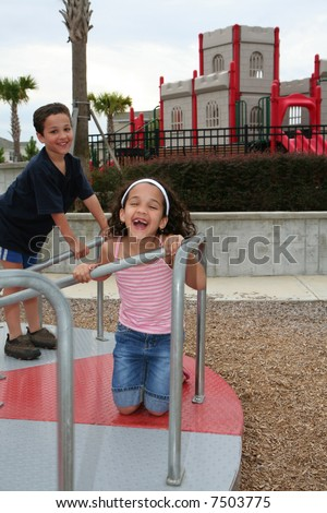 Young girl and boy outside playing on a playground - stock photo