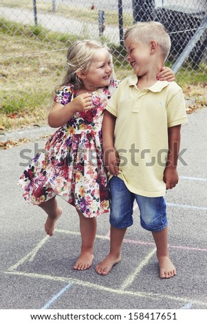 Young girl and boy playing hopscotch, smiling - stock photo
