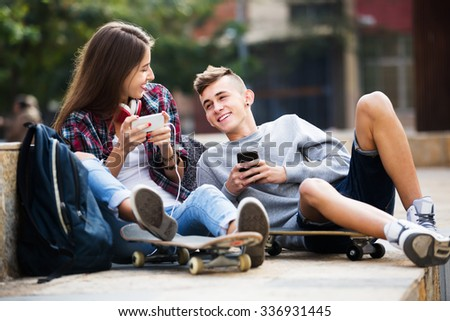 Young girl and boy playing on smartphones and listening to music - stock photo