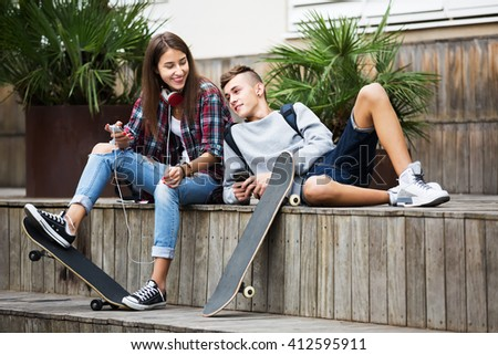 Young girl and boy teens playing on smartphones and listening to music outdoors - stock photo