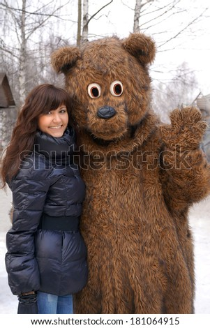Young girl and brown bear on holiday Pancake week in Russia  - stock photo