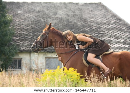 Young girl and chestnut horse portrait near the barn in summer
