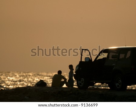 Young girl and fellow on sundown background 3 - stock photo