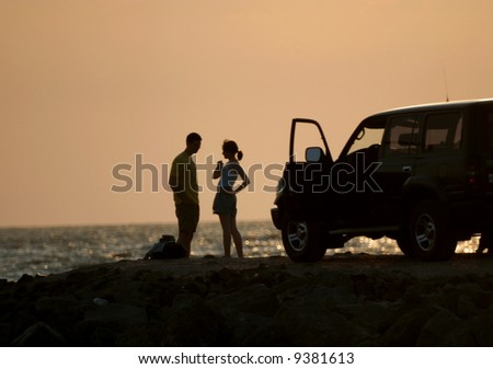 Young girl and fellow on sundown background - stock photo
