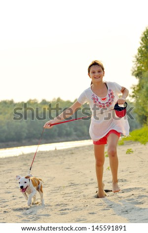 young girl and her amstaff dog running on beach - stock photo