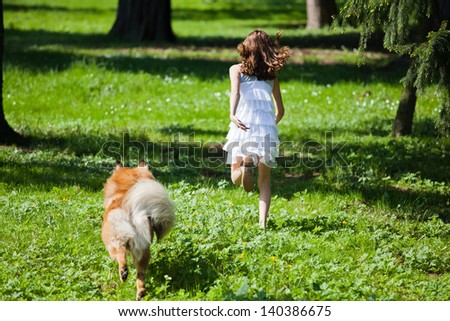 young girl and her Elo dog running on a meadow