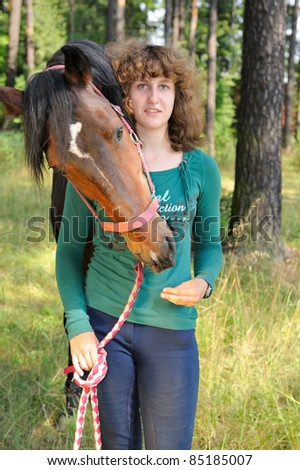 Young girl and her horse nearby. Horse hugs its owner. Girl looks at camera. - stock photo