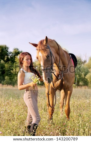 Young girl and horse on a summer meadow