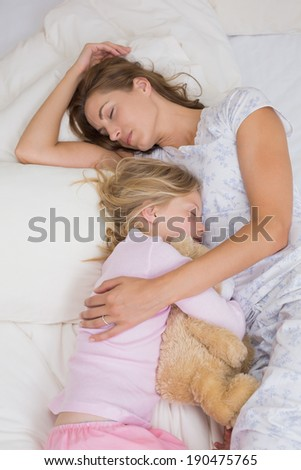 Young girl and mother sleeping peacefully with stuffed toy in bed at home