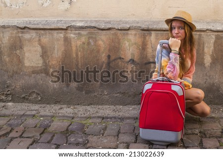 Young girl and red suitcase on the pavement road, travel concept.
