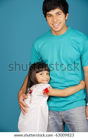 Young girl and young man smiling at camera - stock photo