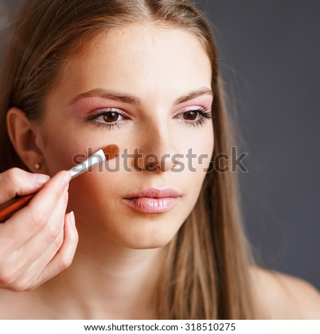 Young  girl applying make-up by make-up artist.