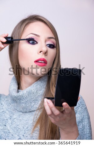 Young girl applying mascara - stock photo